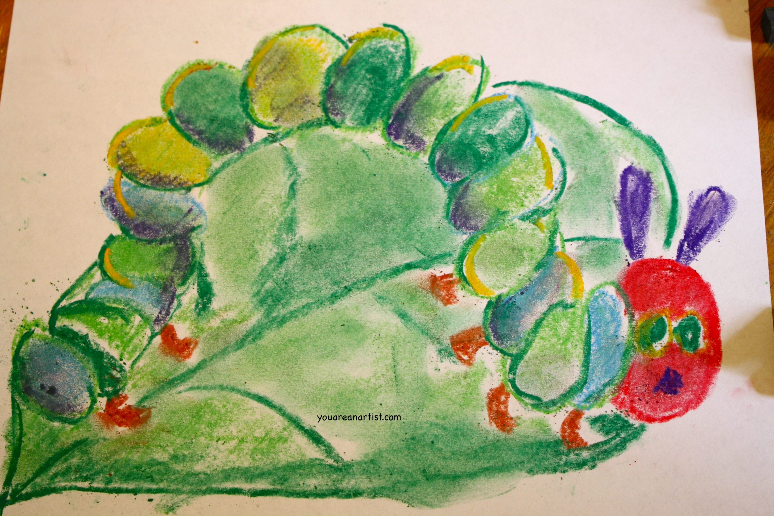 In this art lesson, Nana's granddaughter teaches her how to draw a caterpillar with chalk pastels in the style of Eric Carle's Very Hungry Caterpillar.