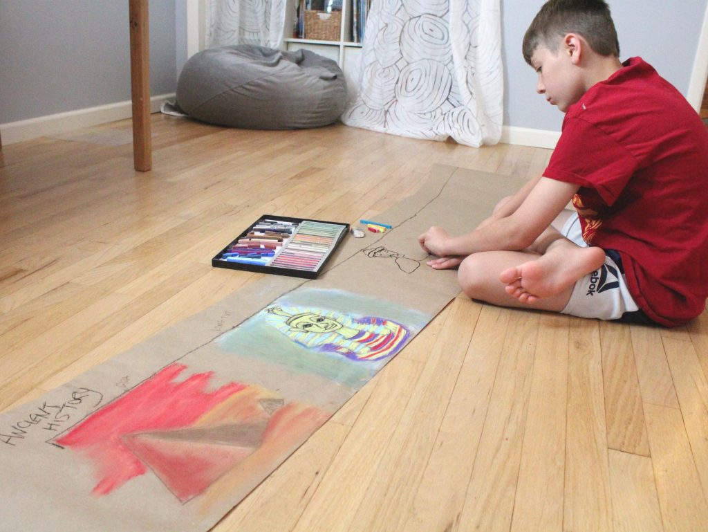 Child drawing on the floor with chalk pastels