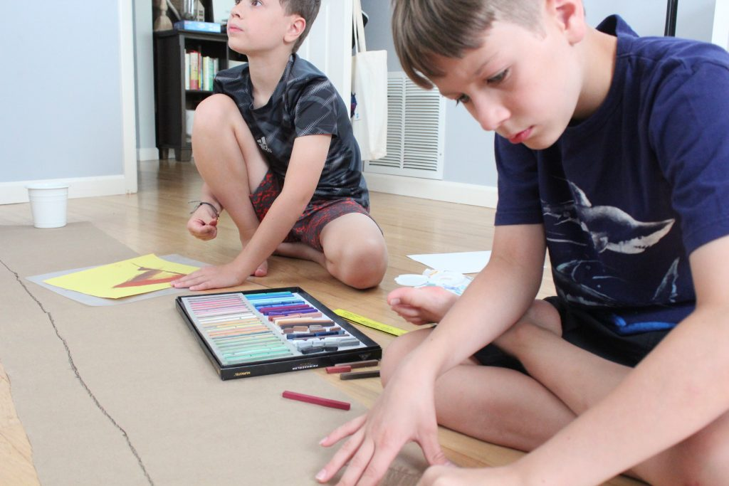 Kids sitting on floor drawing with chalk pastels