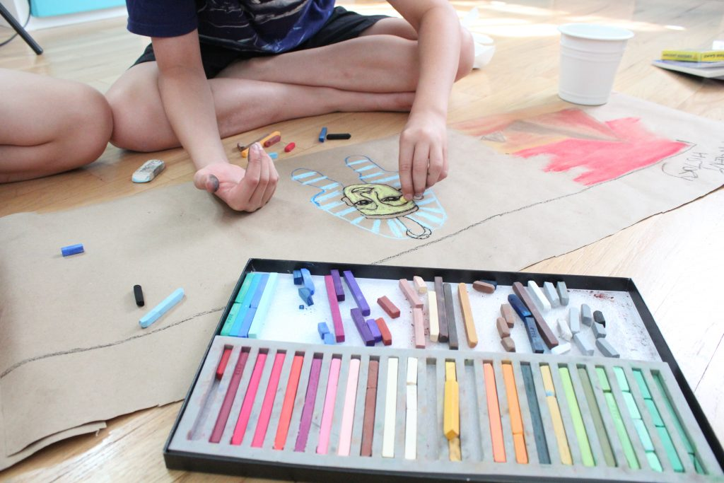 Chalk Pastels on floor with kid hands drawing